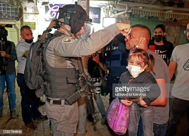 Member of Israeli security forces argues with a Palestinian protester holding a child outside the Damascus Gate in Jerusalem's Old City on May 9,...
