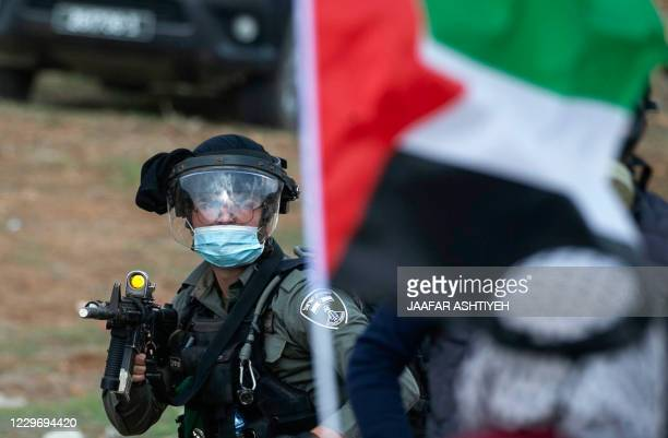 A member of Israeli security forces looks at Palestinian protesters lifting national flags amid clashes following a demonstration against the...