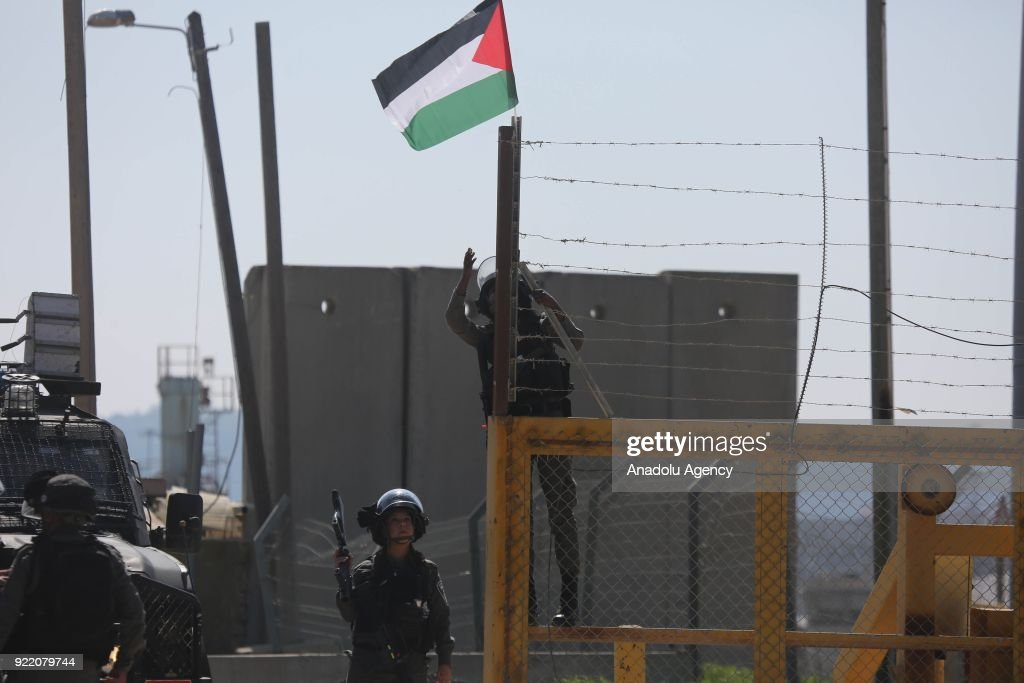 A member of Israeli security forces tries to take down a Palestinian flag as Palestinians stage a protest, organized by Palestine Committee Against the Wall and Settlements, which has connection with Palestine Liberation Organization, against Munzir Amira's detention at Ofer Prison located in west of Ramallah, West Bank on February 21, 2018.