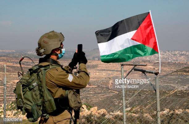 Member of Israel's security forces takes pictures as Palestinian demonstrators try to reach their lands confiscated by Israeli authorities, during a...