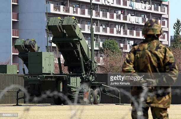 A member of Japan Ground SelfDefense Force stands guard in front of Patriot Advanced Capability3 interceptors upon its compeletion of deployment at...