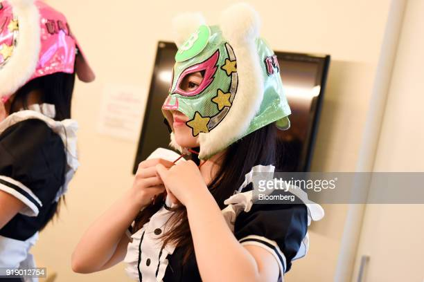 A member of Japanese pop group 'Virtual Currency Girls' adjusts her mask bearing the symbol for the Bitcoin cryptocurrency ahead of performing...