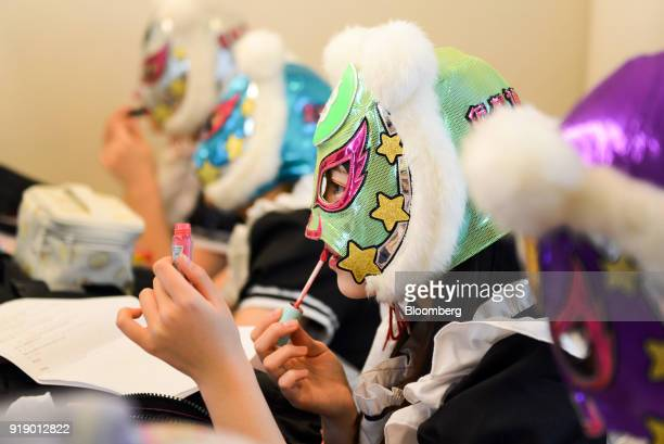 A member of Japanese pop group 'Virtual Currency Girls' applies lip gloss to her lips ahead of performing onstage in Tokyo Japan on Friday Feb 16...