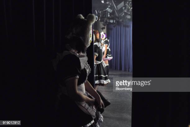A member of Japanese pop group 'Virtual Currency Girls' watches bandmates as they perform onstage in Tokyo Japan on Friday Feb 16 2018 The...