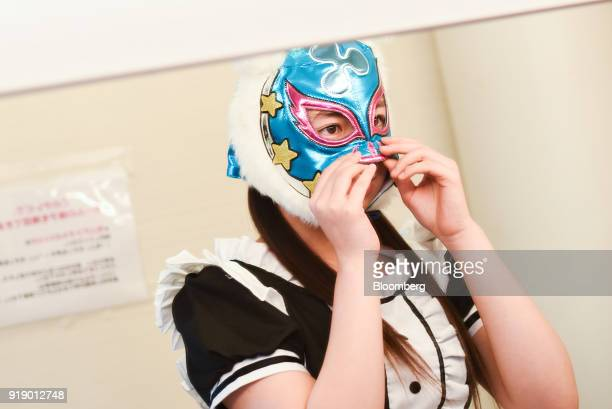 A member of Japanese pop group 'Virtual Currency Girls' wearing a mask with the symbol for the Ripple cryptocurrency adjusts her headgear ahead of...