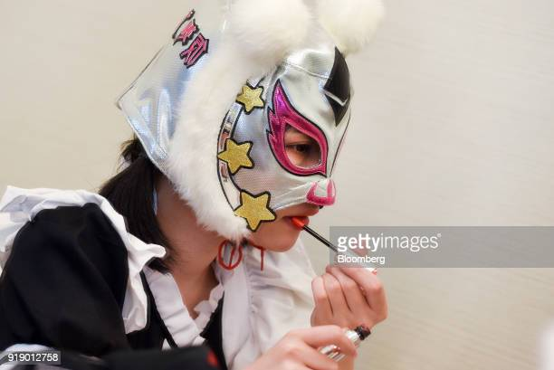 A member of Japanese pop group 'Virtual Currency Girls' wearing a mask with the symbol for the Ether cryptocurrency applies lip gloss ahead of...