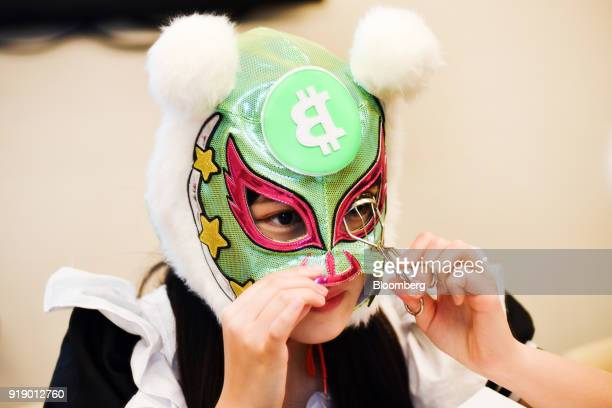 A member of Japanese pop group 'Virtual Currency Girls' wearing a mask with the symbol for the Bitcoin cryptocurrency curls her eyelashes ahead of...