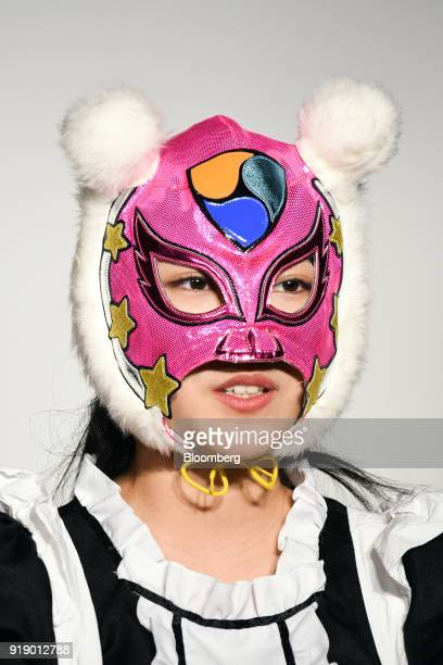 A member of Japanese pop group 'Virtual Currency Girls' wearing a mask with the symbol for the Nem cryptocurrency poses for a photograph in Tokyo...