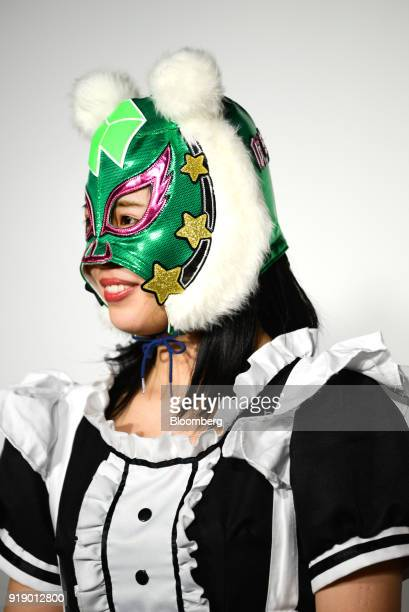 A member of Japanese pop group 'Virtual Currency Girls' wearing a mask with the symbol for the Neo cryptocurrency poses for a photograph in Tokyo...