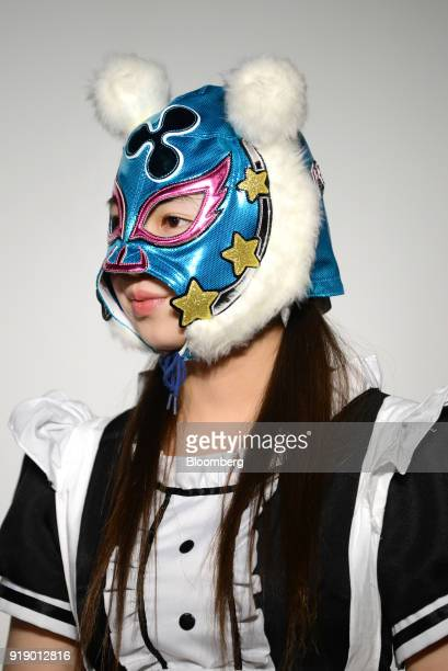 A member of Japanese pop group 'Virtual Currency Girls' wearing a mask with the symbol for the Ripple cryptocurrency poses for a photograph in Tokyo...