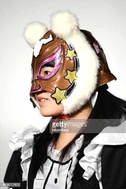 A member of Japanese pop group 'Virtual Currency Girls' wearing a mask with the symbol for the Cardano cryptocurrency poses for a photograph in Tokyo...