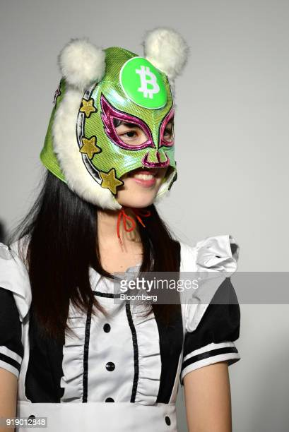 A member of Japanese pop group 'Virtual Currency Girls' wearing a mask with the symbol for the Bitcoin cryptocurrency poses for a photograph in Tokyo...