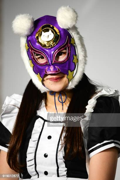A member of Japanese pop group 'Virtual Currency Girls' wearing a mask with the symbol for the MonaCoin cryptocurrency poses for a photograph in...