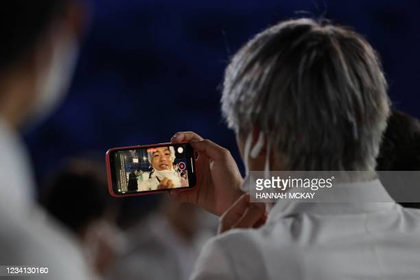 Member of Japan's delegation films with his mobile phone as he enters the Olympic Stadium during Tokyo 2020 Olympic Games opening ceremony's parade...