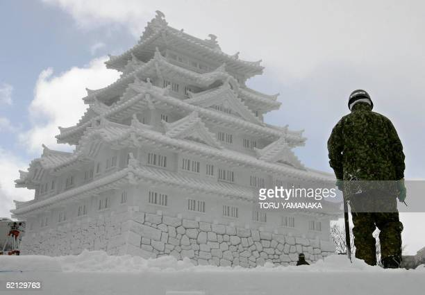 A member of Japan's Ground Self Defence Force stands beside a snow sculpture of Nagoya Castle in preparation for the Sapporo Snow Festival in Sapporo...