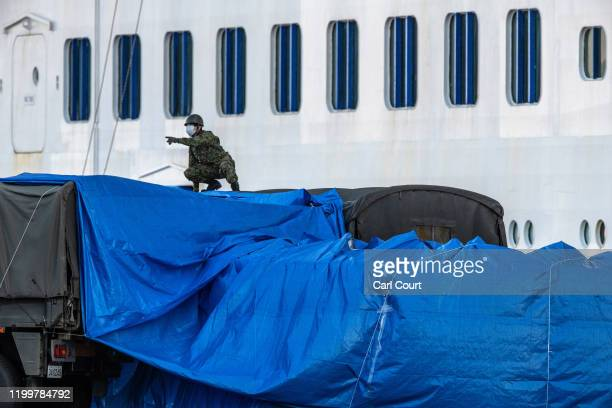 Member of Japans self-defence force works to place tarpaulin over a walkway to a military truck from the Diamond Princess cruise ship at Daikoku Pier...