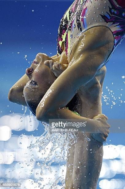 A member of Japan's team is lifted by a teammate as they compete in the team free routine final synchronised swimming event during the 2014 Asian...