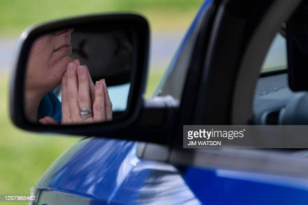 A member of Jesus' Church prays in her car during a Sunday church service held at Great Marsh Park in Cambridge Maryland on March 22 2020 Pastor...