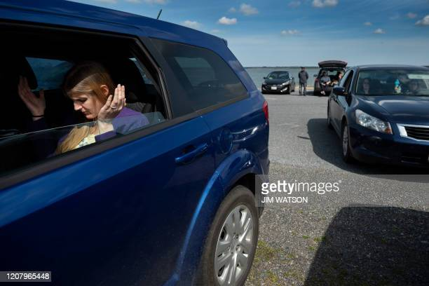 A member of Jesus' Church prays in the back seat of a car during a Sunday church service held at Great Marsh Park in Cambridge Maryland on March 22...