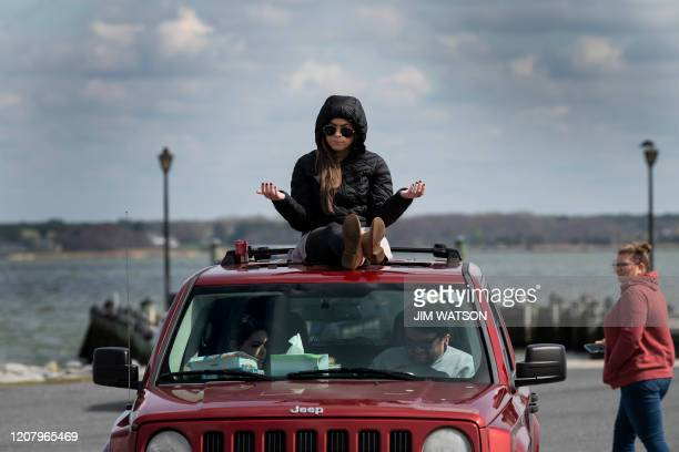 TOPSHOT A member of Jesus' Church prays on top of a car during a Sunday church service held at Great Marsh Park in Cambridge Maryland on March 22...
