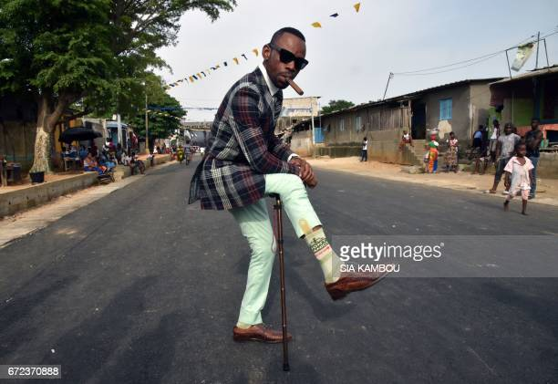 A member of La SAPE movement pose as he parades in a street of Abidjan on April 24 2017 during a day of tribute to late Congolese rumba star Papa...