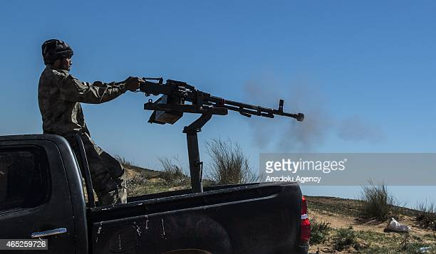A member of Libyan Dawn Coalition takes position with a heavy weapon on a pickup in Zintan region Libya on March 04 2015 Clashes between Libyan Dawn...