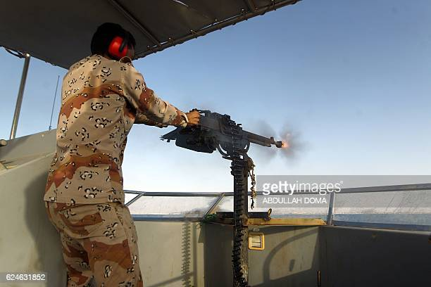 TOPSHOT A member of Libyan naval forces fires towards Islamic State group's positions during a patrol off the coast of Libya's second city Benghazi...