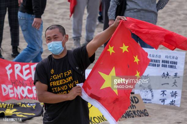 Member of local natives of Hong Kong shows a broken Chinese flag during a flash mob march to show solidarity with the 47 pro-democracy activists in...