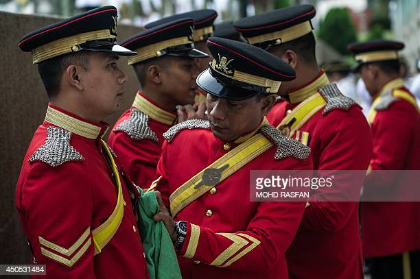 A member of Malaysia's Royal Lance Guard cleans medals before the arrival of Malaysia's King Abdul Halim Mu'adzam Shah during his official birthday...