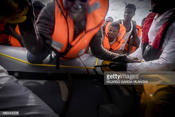 A member of Medecins Sans Frontieres helps migrant to board a zodiac during a rescue operation by the NGO with the Dignity 1 search and rescue vessel...