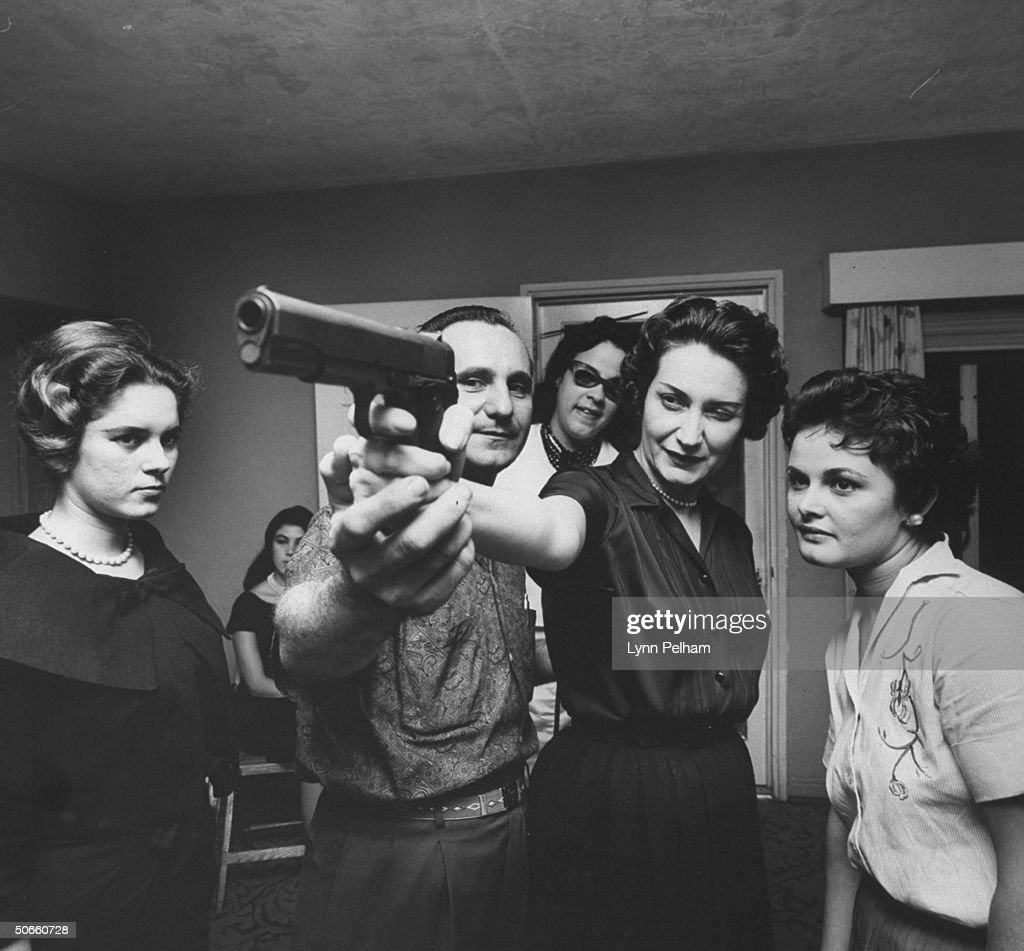 Member of M.R.R. anti-Castro movement Carlos Castaner, teaching women volunteers how to handle firearms.