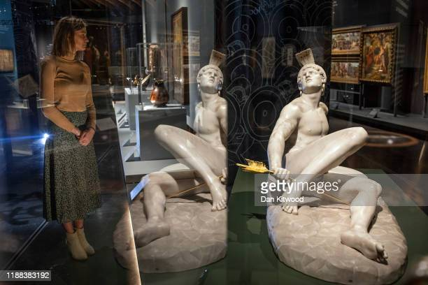 Member of Museum staff poses for another photographer besides a sculpture of Achilles during a press preview of the British Museum's new major...