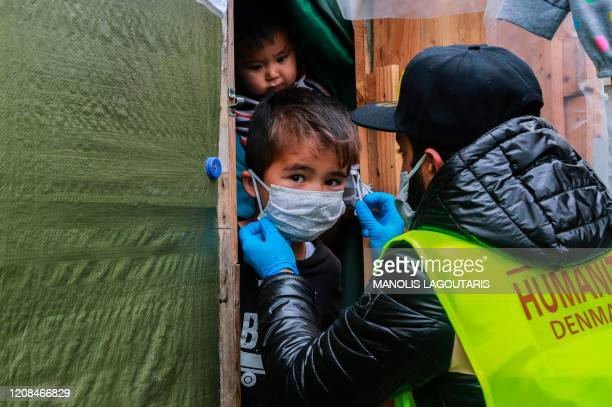A member of NGO Team Humanity shares handmade protective face masks to migrants and refugees in the camp of Moria in the island of Lesbos on March 28...
