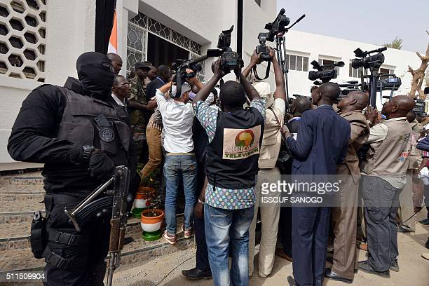 A member of Niger's special forces stands guard as journalists gather around President Mahamadou Issoufou as he leaves the Hotel de Ville in Niamey...