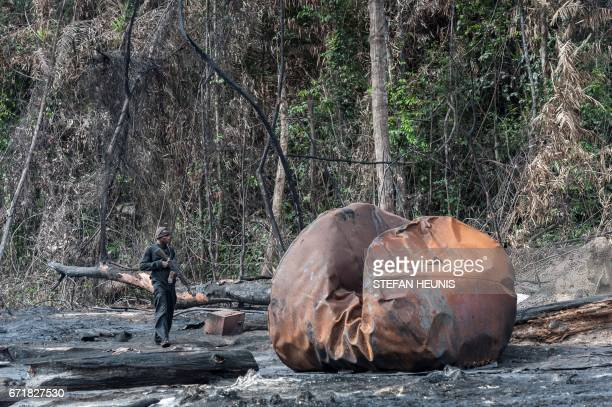 A member of NNS Delta of the Nigerian Navy forces patrols on an abandoned site of an illegal oil refinery in the Niger Delta region on April 19 2017...