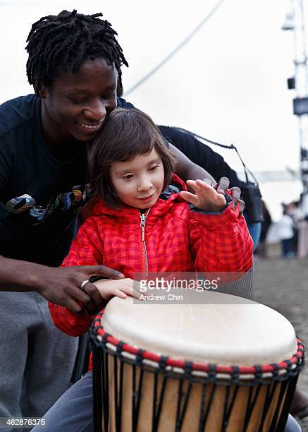 A member of 'Odysseo' cast guides a visually impaired child Alethea Moroney from The Canadian National Institute for The Blind to play the djembe...