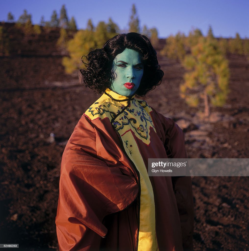 A member of of dance/rock group The Shamen, dressed and made up to resemble Vladimir Tretchikoff's popular painting 'Green Lady' (Chinese Girl), during a video shoot in Spain, circa 1990.