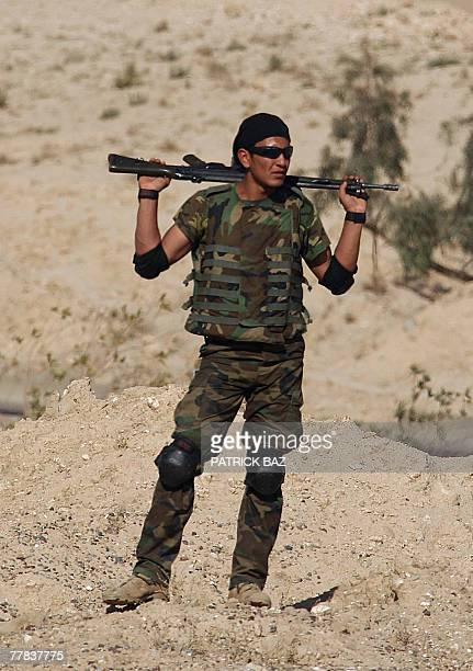Member of one of Iraq's Concerned Local Citizen groups, US sanctioned neighbourhood watch groups, stand guard watching US soldiers with the 101st...