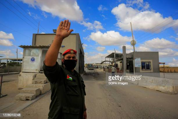 Member of Palestinian Hamas security forces seen wearing a facemask, guides trucks entering the Kerem Shalom crossing in the southern Gaza Strip city...