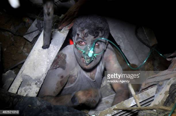 A member of Palestinian Selam family is rescued under the wreckage of their house destroyed by an Israeli airstrike within the 'Operation Protective...