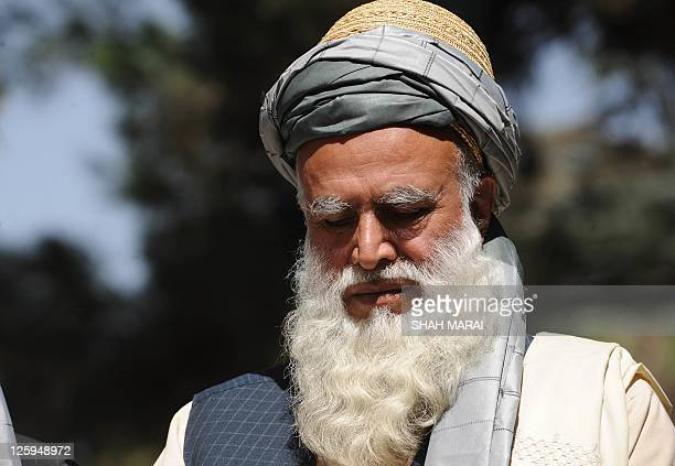 Member of parliament Abdul Rab Rasoul Sayaf or 'Ustad Sayaf' bows his head as he listens to unseen Afghan President Hamid Karzai during a press...