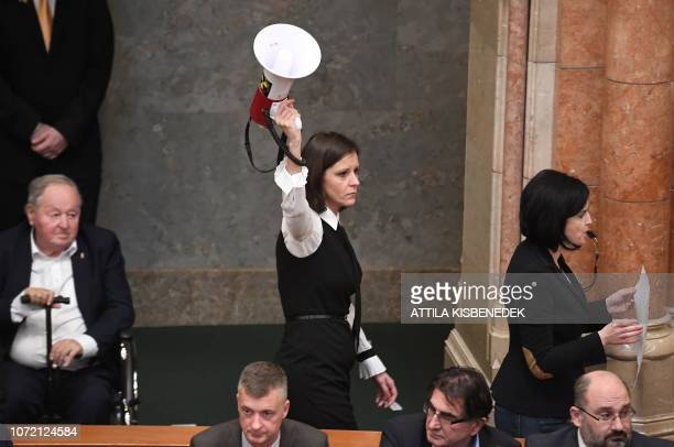 Member of Parliament Bernadett Szel holds a sirenhorn next to Agnes Kohalmi of the Hungarian Socialist Party in the hall of the parliament building...