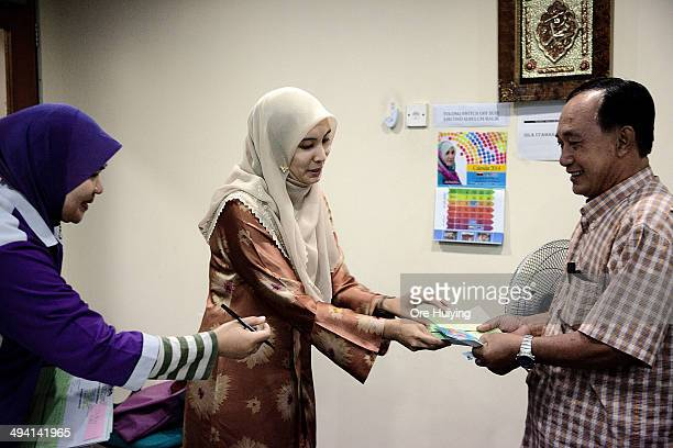 Member of Parliament Nurul Izzah Anwar interacts with a resident of Lembah Pantai in her Parti Keadilan Rakyat office during a weekly...