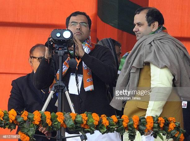 Member of Parliament Parvesh Verma looks through the binoculars as Member of Parliament Maheish Girri waits for his turn before the 'Abhinandan...