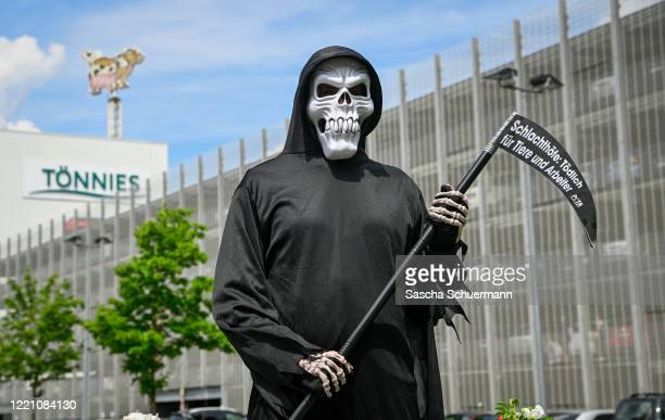 Member of PETA stands in front of the Toennies meat packing plant dressed as the Grim reaper during the coronavirus pandemic in Rheda-Wiedenbrueck on...