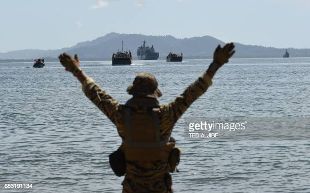 A member of Philippine navy special operations group signals to Philippine landing ships loaded with PhilippineUS marines and civilian volunteers as...