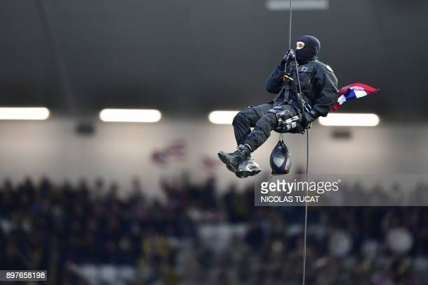 A member of police special force repels onto the pitch with a rugby ball prior to the French Top 14 rugby union match between BordeauxBegles and La...