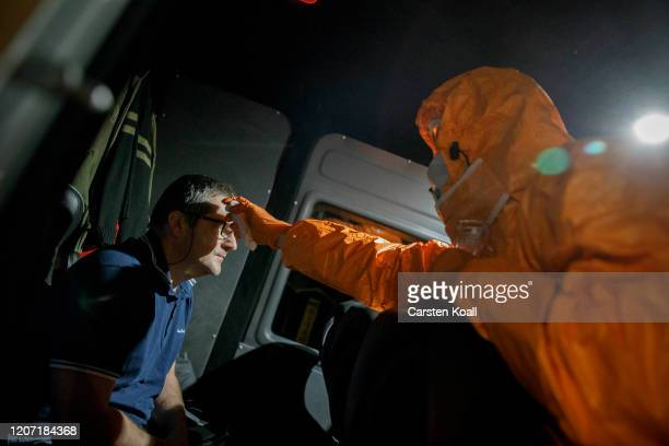 A member of polish the firefighter crew takes the temperature of a passenger of a vehicle coming from Germany to enter Poland hours before the border...