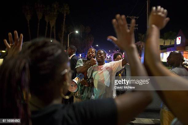 A member of protest security encourages people to stay peaceful in the face of advancing police during protest march in reaction to the fatal police...