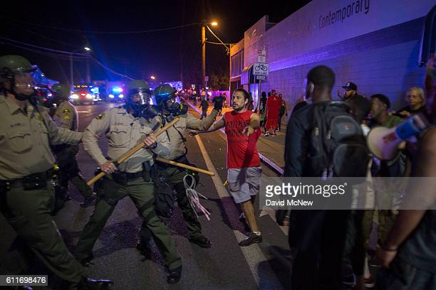 A member of protest security person defuses a potentially volatile moment by stepping between protesters and Sheriffs deputies to maintain a peaceful...